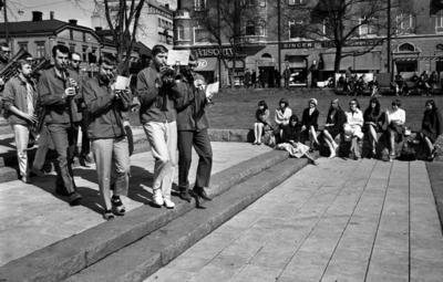 Våren 29 april 1966  En mässingsorkester går spelande genom en park i centrala Örebro. I bakgrunden sitter publik och betraktar dem.