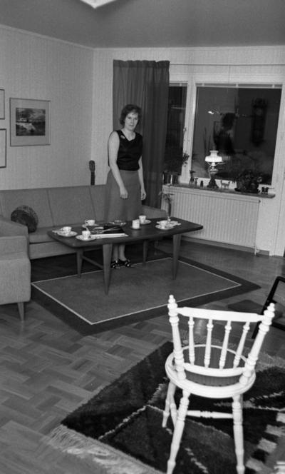 Byggspecial Oxhagen 11 februari 1966  I ett vardagsrum i en lägenhet i Oxhagen står en kvinna klädd i svart linne, grå kjol och sandaler och invid ett bord. I rummet finns en soffa, en fåtölj och en matta under bordet. I förgrunden står en vit stol samt en matta under den. Tavlor hänger på väggarna.
