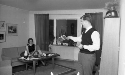 Byggspecial Oxhagen 11 februari 1966  I ett vardagsrum i Oxhagen sitter en kvinna i en soffa. Hon är klädd i svart linne, grå kjol och har sandaler på fötterna. En man står upp i förgrunden till höger invid en bokhylla. Han är klädd i vit skjorta, svart väst, svart slips och grå byxor. Han håller en bok i sin högra hand och håller upp den mot kvinnan. Uppe på bokhyllan ligger en pickelhuva. I bakgrunden syns fönster med gardiner. På väggarna hänger det tavlor.