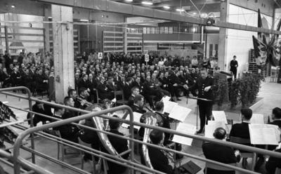 Julreportage, United Shoe 3 februari 1966  En dirigent står framför en orkester och dirigerar. De befinner sig inne i en fabrikslokal. Bakom dirigenten står ett podium på en upphöjd plats. I bakgrunden till vänster sitter publiken som består av en massa herrar i kostymer samt längst bak står arbetare i overaller. Vid sidan till höger om herrarna som sitter står ett antal andra herrar i kostymer samt damer.