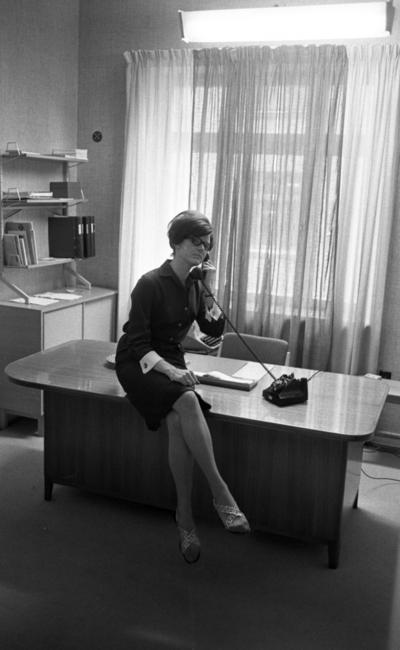 Telefonreportage,31 januari 1966  En kvinna sitter på kanten på ett bord och talar i telefon. Telefonen är svart. Kvinnan är klädd i en kort klänning och har sandaler på fötterna. I bakgrunden finns ett fönster med gardiner runt omkring.