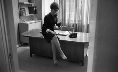 Telefonreportage, 31 januari 1966  En kvinna sitter på kanten på ett bord och talar i telefon. Telefonen är svart. Kvinnan är klädd i en kort klänning och har sandaler på fötterna. I bakgrunden finns ett fönster med gardiner runt omkring.