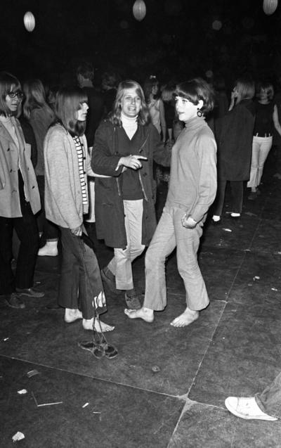 Popgala 6 juni 1966  Närbild på tre flickor ur publiken under en musikföreställning klädda i blusar, tröjor och byxor. Flickan i mitten bär kappa. Två av flickorna är barfota. Flickan till höger håller snörena till ett par sandaler i sin högra hand.