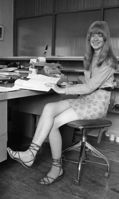 Kort- kort på jobb 2 augusti 1966  En ung kvinna med långt hår, långärmad tröja, kort kjol och med sandaler på fötterna sitter på en stol inne på ett kontor. Hon håller i en bok som ligger uppslagen framför henne på skrivbordet. En räknemaskin står också på skrivbordet.
