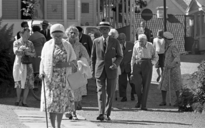 Loka brunn 2 22 juli 1966  En massa äldre damer och herrar på promenad i kurorten Loka brunn. En av damerna sitter i en rullstol. Damerna bär klänning och herrarna bär kostym. I bakgrunden syns byggnader samt bilar.