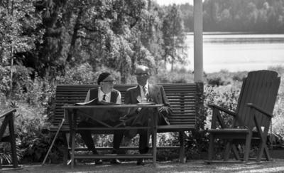 Loka brunn 2 22 juli 1966  Två äldre herrar sitter på en bänk utomhus nära vattnet i kurorten Loka brunn. Mannen till vänster är klädd i vit skjorta, mörk väst, svart slips och mörka byxor samt en svart basker på huvudet. Han bär även glasögon. Mannen till höger bär ljus, randig kostym, vit skjorta och mörk slips. Även han bär glasögon. Framför bänken står ett bord och två stolar syns på ömse sidor om bordet.