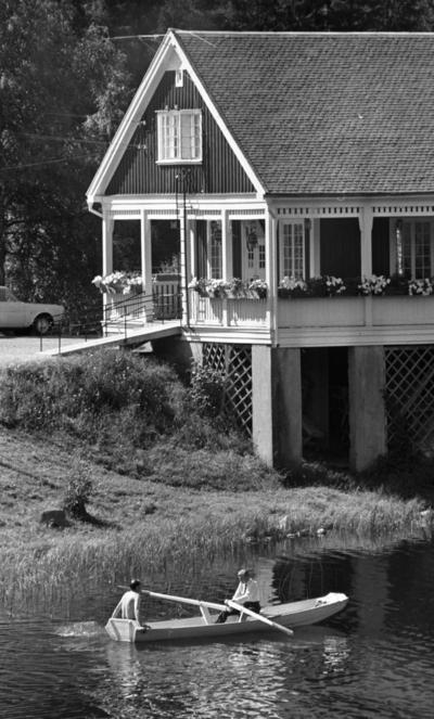 Loka brunn 2 22 juli 1966  Två herrar varav den ena har bar överkropp och den andra är klädd i vit skjorta, mörk slips och mörka byxor är ute i en eka i vattnet nära Loka brunn. Mannen i skjorta ror. I bakgrunden syns ett hus med en bil parkerad nära intill.