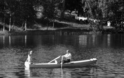 Loka brunn 2 22 juli 1966  Två herrar varav den ena har bar överkropp och den andra är klädd i vit skjorta, mörk slips och mörka byxor är ute i en eka i vattnet nära Loka brunn. Mannen i skjorta ror. Mannen med bar överkropp vinkar till fotografen. Kläder som hänger på tork på en tvättlina syns i bakgrunden.