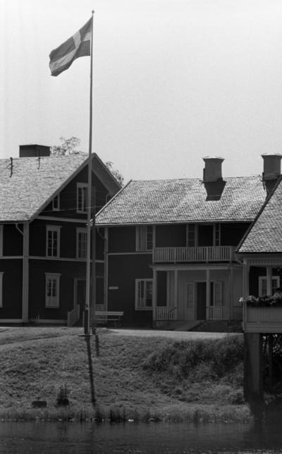 Loka brunn 2 22 juli 1966  Bild på byggnader i kurorten Loka brunn. En svensk flagga är hissad på en flaggstång framför husen. Ett vattendrag syns i förgrunden.