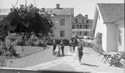 Loka brunn 22 juli 1966  Äldre damer i klänningar samt äldre herrar i kostymer promenerar utanför byggnader på kurorten Loka brunn. I bakgrunden syns två bilar som står parkerade. Till höger syns ett litet fyrkantigt bord som är dukat med fyra kaffekoppar och fat. En stol samt en bänk står intill bordet.