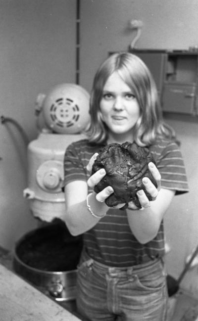 Loka brunn 22 juli 1966  En ung kvinna klädd i randig t-shirt samt jeans håller en stor klump i sina händer. I bakgrunden syns en stor maskin.