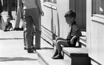 Kvar i stan 26 juli 1967  Ett antal människor befinner sig i centrala stan i Örebro. Närbild på en liten pojke i fyraårsåldern klädd i svarta hängselshorts, randig T-tröja, mörka strumpor och mörka sandaler som sitter på en liten trappa. Ytterligare en liten pojke sitter längre bort i bakgrunden. Vuxna människors ben syns på bilden även.