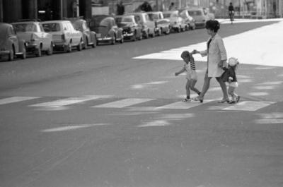 Kvar i stan 26 juli 1967  En mamma klädd i vit kappa, mörk klänning och vita skor går över ett övergångsställe på en gata i centrala Örebro med två små barn- en vid vardera handen. Pojken är klädd i en vit kortbyxdress, randig T-shirt, mörka strumpor och vita sandaler och flickan har vit sjömansmössa på huvudet, rutig kort kappa, vita underbyxor, vita strumpor och svarta skor.