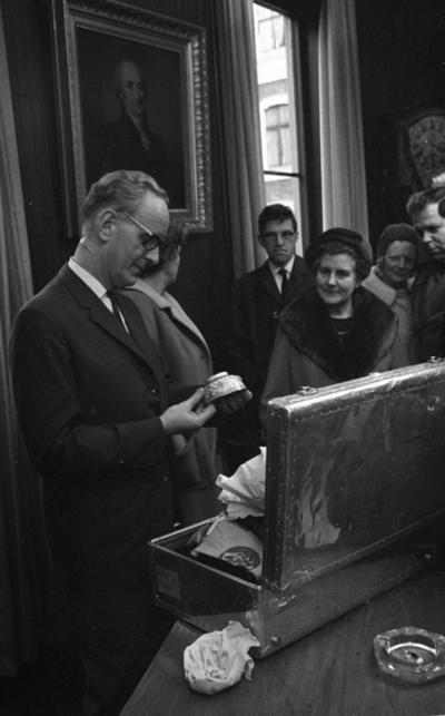 Mingporslin, Maranata, Strejken 25 oktober 1966  En man står i förgrunden i ett rum och tittar på en skål av Mingporslin. Han är klädd i svart kostym, vit skjorta och mörk slips samt bär glasögon. Nedanför honom på ett bord står en stor resväska i silverskimrande metall fylld med mer porslin. En askkopp i glas med en fimpad cigarrett i står också på bordet till höger. Fler herrar och damer står i bakgrunden. En stor tavla föreställande ett porträtt av en man hänger på väggen i bakgrunden.