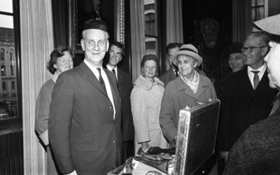 Mingporslin, Maranata, Strejken 25 oktober 1966  En äldre man står i förgrunden i ett rum med en lustig rund mössa på huvudet. Han är klädd i ljus kostym, vit skjorta och ljusrandig slips. Nedanför honom på ett bord står en stor resväska i silverskimrande metall fylld med mer mössor. Fler äldre herrar och damer syns i bakgrunden. En stor tavla föreställande ett porträtt av en man syns i bakgrunden.