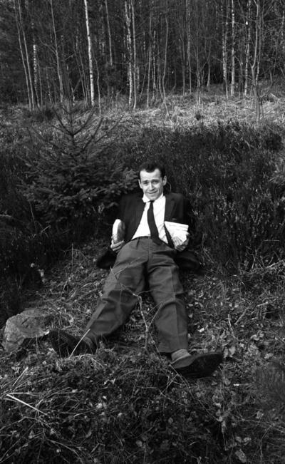 Jobbet och vi, Snickerifabrik 18 maj 1965  En man i kostym som ligger på backen vid en skogsdunge.