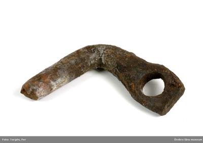 Föremål påträffade vid restaureringen och konserveringen år 2006 av Munkarnas mur, Ramundeboda kloster, fornlämning nr. 8. Föremål nr. 6: vinkelböjd, kraftig järnten, vars ena ände är tillplatad med ett runt hål i. Mått: l. ena skänkeln 9,5 cm, den andra skänkeln (med hålet) 10 cm, diameter 2,2 cm, hålets diameter 2 cm. Exempel på lösfynd från södra murens västligaste del, som var omlagd och kallmurad. Dnr: 2003.230.145 Dessa föremål har endast förtecknats och fotografats, varefter de slängts. (En del av föremålen har tagits emot av ÖLM och införlivats i museets samlingar, ÖLM 38.767:1-2, ÖLM 38.768:1-2 och ÖLM 38.769)