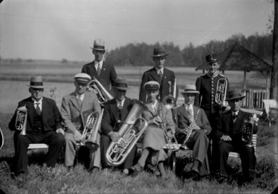 Gruppbild, nio män med musikinstrument. Svennevads musikkår, 1930-1940-talet. Identifiering av personerna finns i Erik Hallbergs skrift