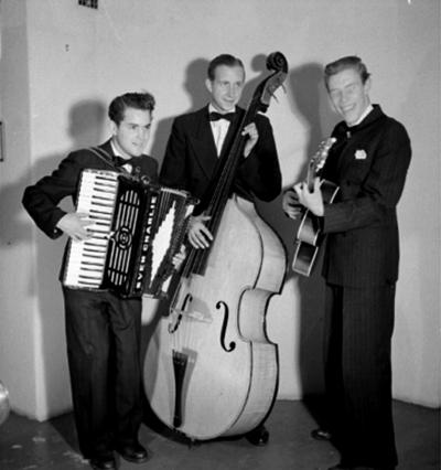Swing-trio, tre män med musikinstrument (dragspel, bas och gitarr). Sven Charlies Ensemble, Örebro. Fr. v. Sven Charlie Falk, dragspel och piano. Arne Olows, bas. Lasse Karlsson, gitarr och trumpet.