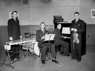 Fyra män med musikinstrument, Olle Bratting & Co. Olle Bratting: vibrafon; Helgesson: klarinett; Harry Törnblom: piano; Algot Larsson: violin. Konsum.