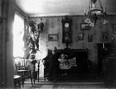 Rumsinteriör, en man och en flicka. Anders Johan Pettersson (givarens farfar) och Kerstin Pettersson (givarens faster)