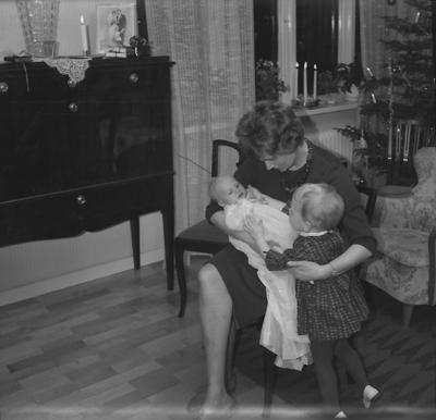 Rumsinteriör, en kvinna och två barn. Barndop. Gunilla Lagerblad och barnen Mats Lagerblad och Ann Lagerblad.