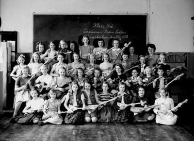 Vasaskolan, klassrumsinteriör, 34 flickor med trängmusikinstrument, med lärarinna Karin Sahlin. Klass 4d, sal 4, 9, 20.