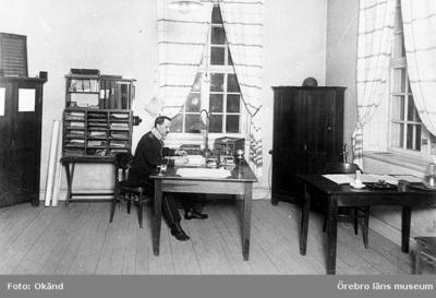 10:e kompaniets expedition vid I3 kasern III Kliszow 1924. Kompaniadjuntant fanjunkare A.W. Lindström iförd uniform modell äldre (1865) sitter vid det stora skrivbordet. Vid det lilla skrivbordet till höger satt kompanichefen då han besökte kompaniet. Med uniform modell 1910 med trekantshatt och gevär modell 1896.