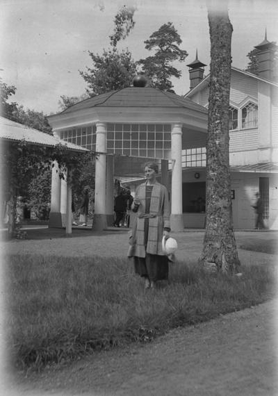 Porla brunn, en kvinna framför byggnaden.