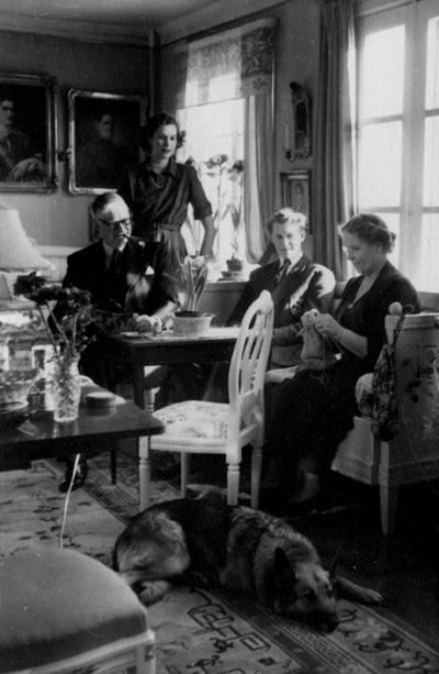 Rumsinteriör, familjegrupp fyra personer och en hund. Familjen Mannerfeldt: far, mor, Anna Nora, Christer.