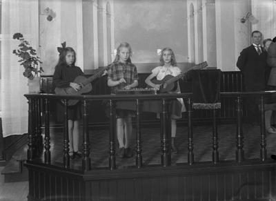 Interiör av Betel kapellet i Fellingsbro, tre flickor med musikinstrument. Från vänster: Anna-Lisa Karlsson, Maj Rubensson, Kerstin Pettersson.