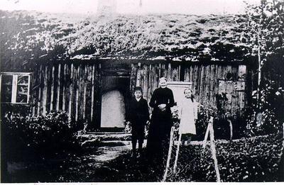 Åsarps sn. Spånggården. Brunabergsslätt, friköpt torp som tillhör Spånggården, Åsarp. Louisa Lood med två barnbarn, föräldralösa, som bodde i stugan. Foto omkring 1915. Louisa Lood var syster till kortets ägare Gunnar Hammars, farfar Anders Johansson. Stugan finns inte bevarad.