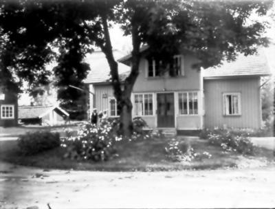 Floby mejeri, bostadshuset. Mejerist Göran Johansson med fru Signe och sonen Halvard.Till vänster Hofflanders möbelaffär. Vid trädet bildades Floby IF 1925.