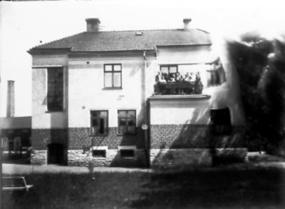 Baksidan av Skaraborgsbankens hus. På balkongen samma personer som på bild 28-6. Gamla mejeriets skorten i bakgrunden. (bilden skadad i kanten)