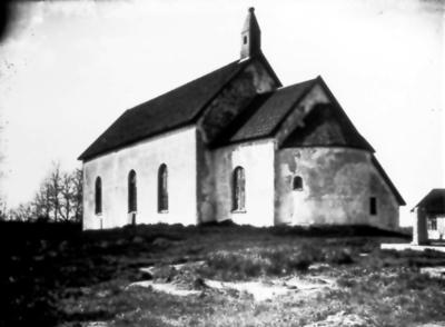 Gökhems kyrka. Skorstenen i form av ett kyrktorn, togs bort 1946-47 då man satt in eluppvärmning. Till höger syns skolhuset.