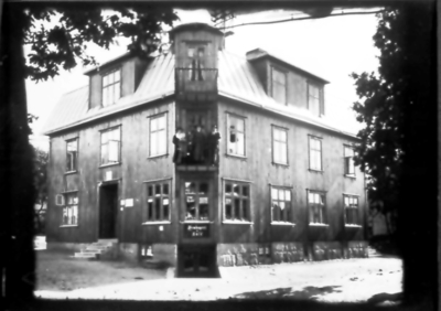 Oskar Blomgrens hus, Storgatan 59, han står på balkongen. Telefonstationen var inrymd här från 1921. I källaren Ana Blomgrens hembageri och café. Huset ersatte smeden Stålhandskes hus.
