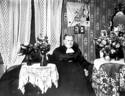 Troligen barnmorksan Carolina Söderlund (1873-1935). På väggen USA:s flagga, kan vara från dottern Ingeborg som emigrerat.