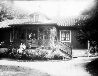 Stinsbostaden vid Floby station. På verandan stinsen Per Johan Sander och hans hustru Algnes Maria Björkman. Framför fosterdottern Gudrun (
