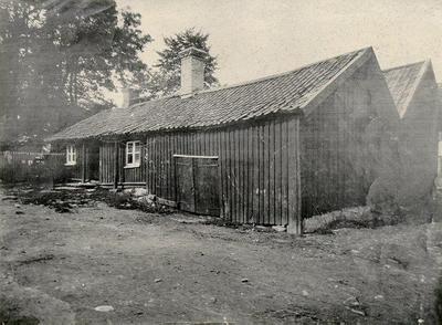 Wallanders bagarstuga t.v. Gården kallades Wallanderska gården men tillhörde Frans Eriksson. Gränsade till Storgatan 7-9. Revs 1911. Nils Janssons gård och magasin t.h. Sedan 1928 Sparbankens fastighet.