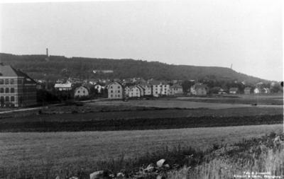 Botvidsgatan. Från nuvarande Midgårdsgatan närmast plan för Medborgarplatsen. Till vänster folkskolan, till höger Tåstorpsgatan. Som synes var det 1930 betydande åkrar där det nu finns tät bebyggelse.