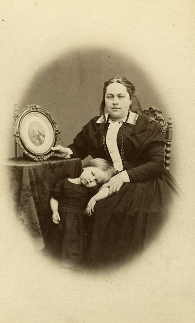 En kvinna och en liten flicka. Doktorinnan HILMA Wilhelmina Ingelson (1831-1901), född Uddén, med dottern Helfrid. Hilma Wilhelmina Uddén, född 1831-12-09 i Stenkvista (D), gift 1862 (?) i Kumla med WILHELM Anders Ingelson, född 1822, provinsialläkare i Tanum, Bohuslän, död 1868 i Hoghem, Tanum, O. Dottern: Helfrid Ingelson, född 1866-05-08 i Hoghem, Tanum, gifte sig med läkare Fredrik Bissmark, som avancerade till medicinalråd. Eftersom Hilma blev änka 1868 kan hon ha flyttat till sin bror Axel Uddén i Strängnäs. Han gifte sig 1868 när han hade fått tjänst som läroverksadjunkt där. Fotografiet måste vara tagen runt 1868-1869, med tanke på att hon är änka på bilden och förmodligen sitter med ett porträtt av sin döde make, och flickan ser ut att vara i 2-3 årsåldern.