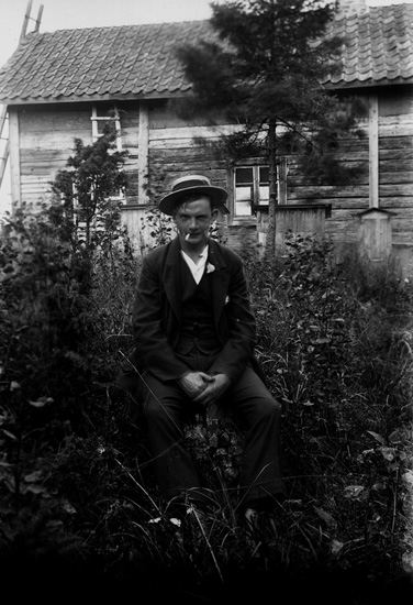 En man. Envånings stuga i bakgrunden. Rökare i naturen. Artur Franzén