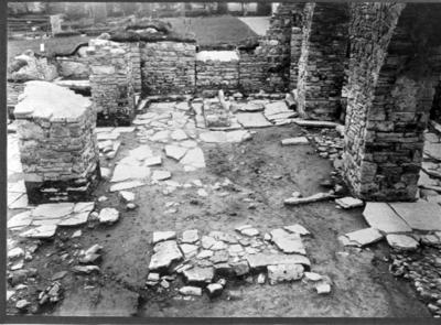 Kyrkan. Långhuset. Gamla golvet blottlagt. Roten av en rest sten (sandsten). Helga kors-altarets grund. Foto mot väst.