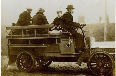Falköpings första trafikomnibuss. Kusken. Hilma Angnes Strandberg och hennes man. Stans första buss gick mellan Falköpings torg och Mössebergs portar. (En bland landets äldsta busslinjer) .Obs. Bussen har helgjutna däck. År 1908 bildades i staden Falköping - Mössebergs bilaktiebolag.