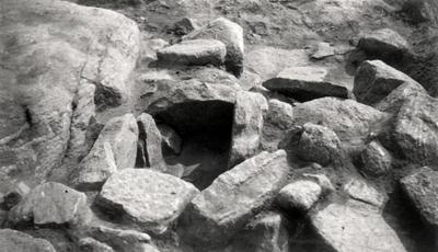 Norra Vånga sn. Grav intill jordfast sten. Yngre järnåldern. Hortstätning för gravkärl av trä. Brända ben.