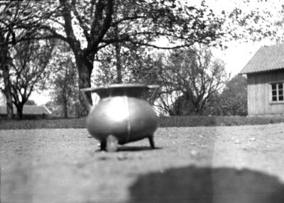 Från Stensholmen, Vartofta-Åsaka. Urna av metall hittad vid kanalrensning i Ätran för flera år sedan. Ännu en finns på gården.
