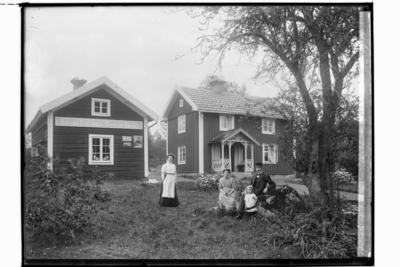 Tvåvånings enkelstuga med veranda med snickarglädje. Flygelbyggnad innehållande lanthandel, 4 personer framför byggnaden. Konrad Eriksson