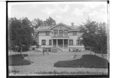 Tvåvånings bostadshus med balkong, veranda och frontespis. En man med stor hund framför huset. Fabrikör Karl Gillberg.