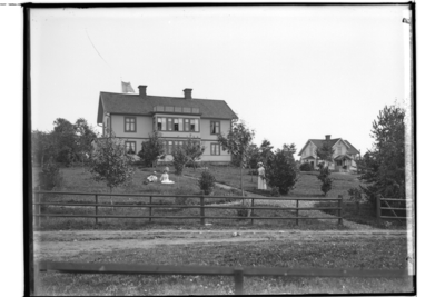 Tvåvånings bostadshus med glasad balkong och glasad veranda. En och en halvplans bostadshus med frontespis och veranda i snickarglädje. 3 personer i trädgården. Emil Pettersson. Till vänster nuvarande Binninge gård 1.