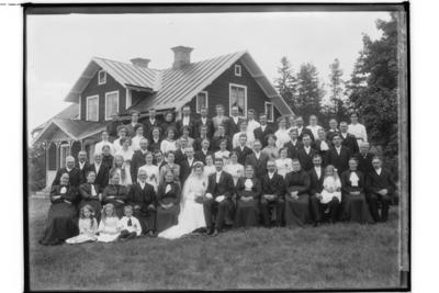 Bröllop, brudpar och bröllopsgäster. En och en halvplans bostadshus med frontespis och veranda med snickarglädje. Gustaf Pettersson